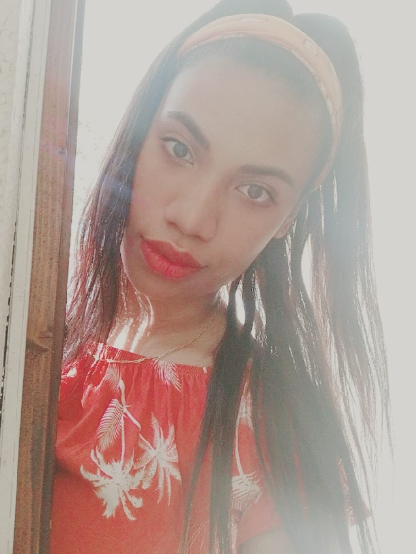 Young Malagasy woman wearing red lipstick and a red top.